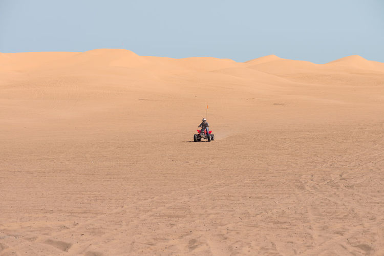 Man Riding Quadbike In Desert Against Clear Sky