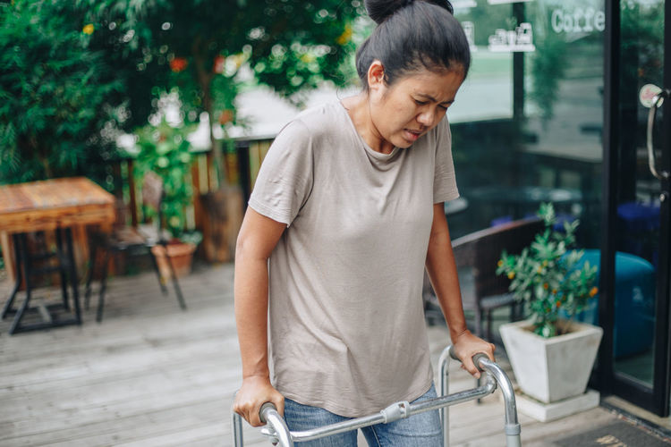 Woman walking with mobility walker on footpath
