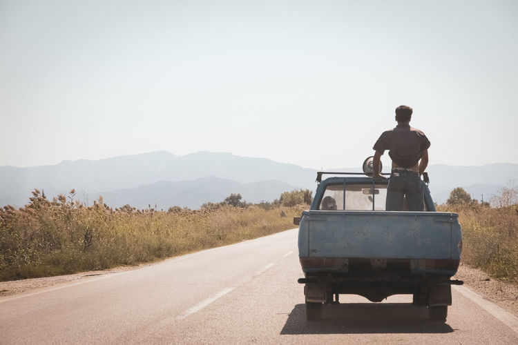 Rear view of man on road against clear sky