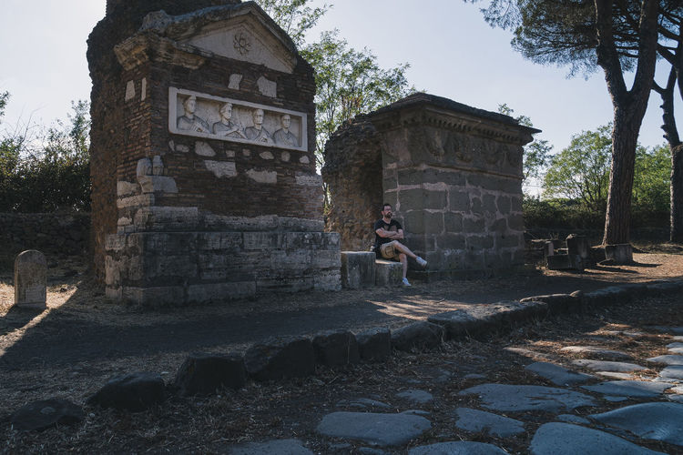 Woman in front of old ruin against sky