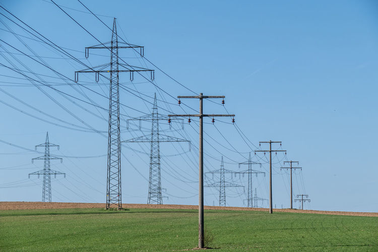 Electricity  Cable Technology Electricity Pylon Power Line  Power Supply Sky Fuel And Power Generation Connection Land Field Nature Landscape Environment No People Grass Day Clear Sky Low Angle View Outdoors Electrical Equipment Complexity