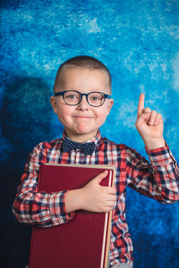 Portrait of cute boy holding eyeglasses