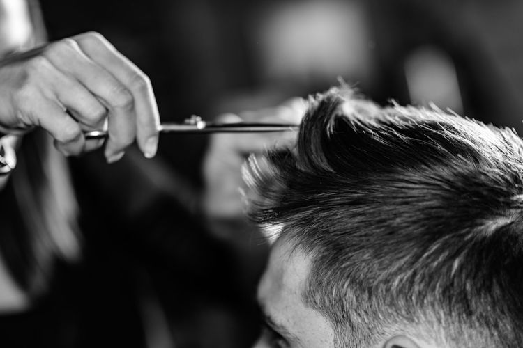 Cropped hand of woman cutting man hair at shop