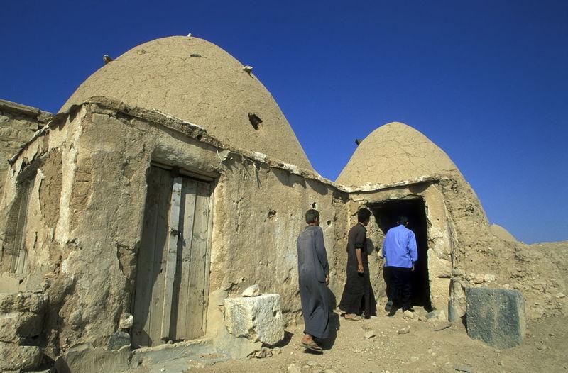 Men Entering Abandoned Adobe House