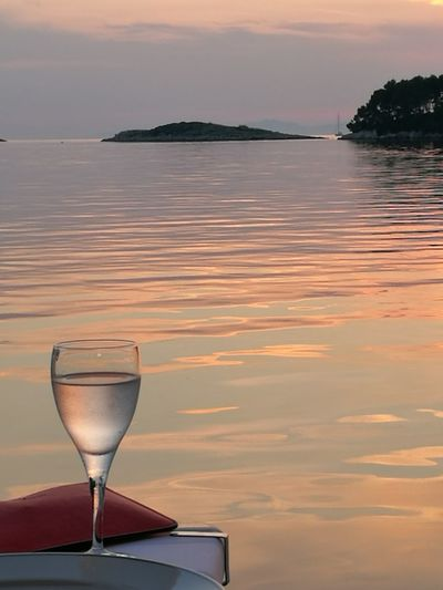 Wineglass against sea during sunset