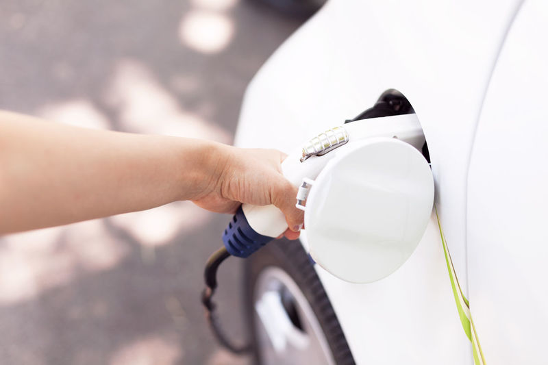 Cropped hand of woman charging electric car at station