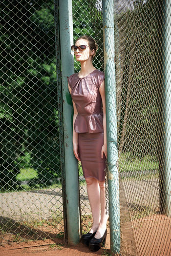 Woman in sunglasses standing by fence