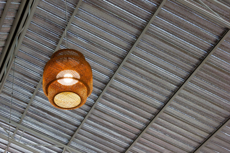 Low angle view of illuminated lamp hanging on ceiling