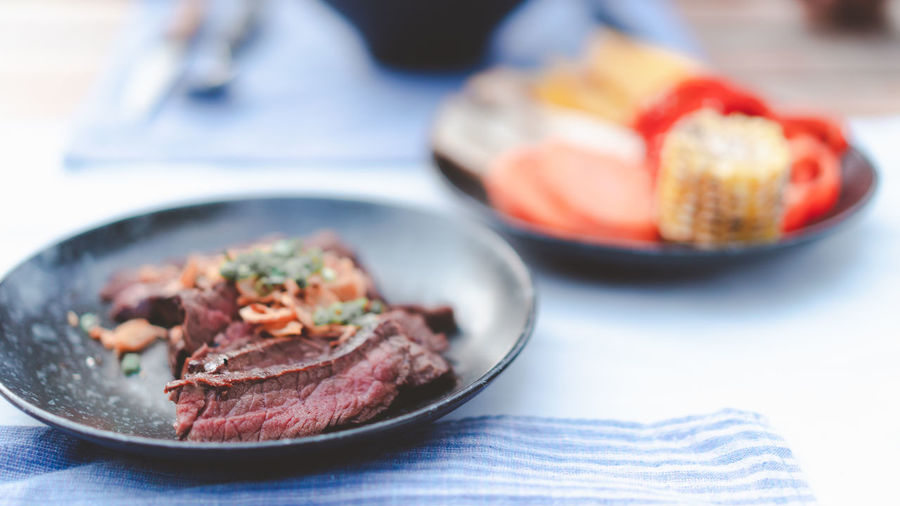 delicious medium rare grilled beef cut on black dish, restaurant decorated style for bbq menu design Barbecue BBQ Beef Burn Decoration Delicious Dinner Eat Food Fresh Gourmet Grill Meal Meat Medium Menu Pink Raw Restaurant Roaster Steak Stove Vegetable