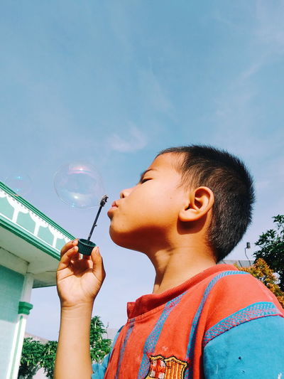 Low angle view of boy blowing bubble against sky during sunny day