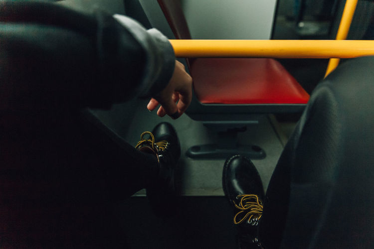 Low section of man wearing shoes in bus