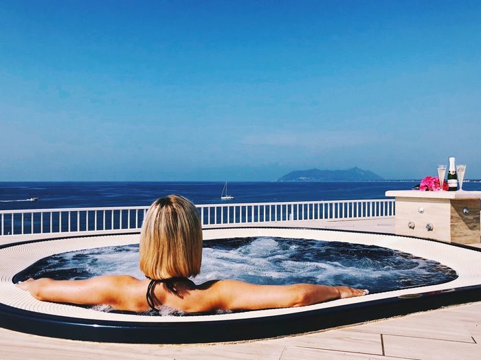Rear view of woman relaxing in swimming pool against sea