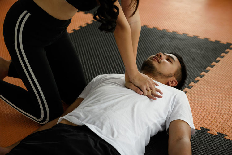 Midsection of woman pressing man chest