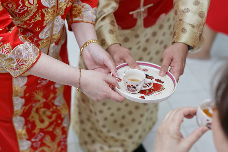 Chinese wedding couple holding tea cup during tea ceremony Groom Tea Ceremony Chinese Wedding Wedding Bride Togetherness Celebration Holding Wedding Close-up Wedding Ceremony Wedding Dress Bridegroom Wedding Reception Newlywed Ceremony