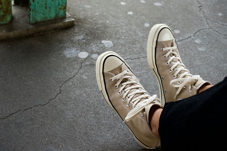 Low section of person wearing shoes on footpath