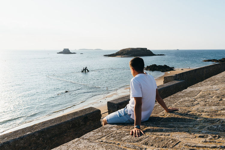 Side view of teenage boy looking at sea while sitting on retaining wall against clear sky