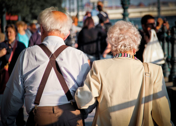Rear View Of Senior Couple Walking In City