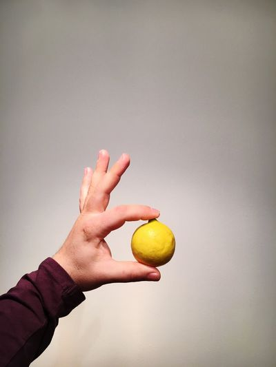 Close-Up Of Hand Holding Lemon