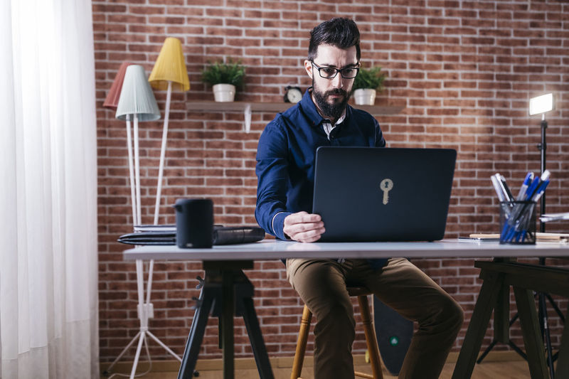 Adult elegant man in eyeglasses sitting at table in modern office and using laptop with concentration. At Home Working Beard Business Businessman Communication Computer Desk Eyeglasses  Indoors  Internet Laptop Lifestyles Men Occupation Office One Person Real People Sitting Table Technology Using Laptop Wireless Technology Working Young Adult