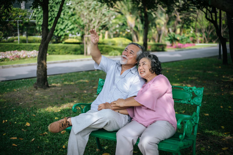 Adult Arm Around Bonding Couple - Relationship Emotion Females Happiness Leisure Activity Lifestyles Love Mature Adult Mature Men Outdoors Park Plant Positive Emotion Real People Senior Adult Sitting Smiling Togetherness Tree Two People Women