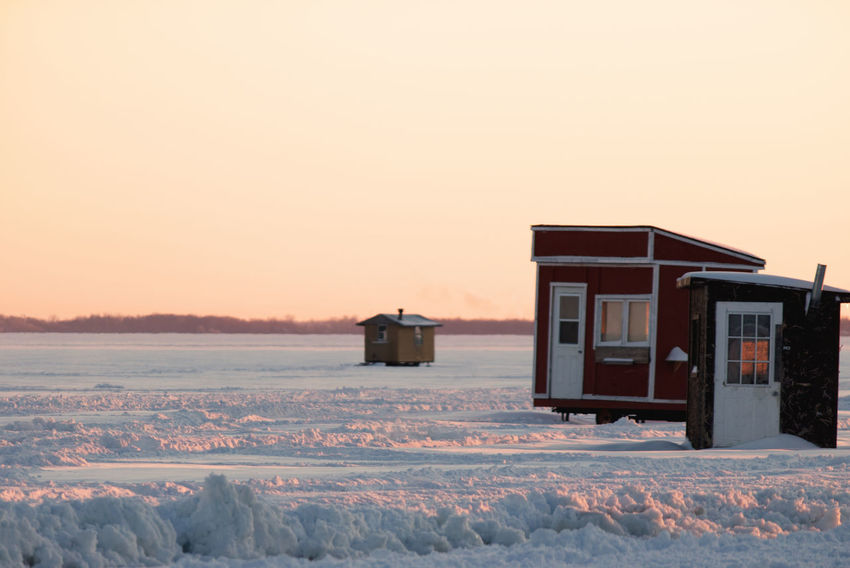Three little huts on a frozen lake waiting for their tenants to come ice fishing. Frozen Lake Frozen Lake At Sunset Frozen Lake Surface Ice Fishing Beauty In Nature Clear Sky Cold Temperature Day Frozen Ice Ice Fishing Huts Ice Fishing Huts On Frozen Lake At Sunset Landscape Nature No People Outdoors Scenics Sky Snow Snowdrift Sunset Transportation Weather Winter