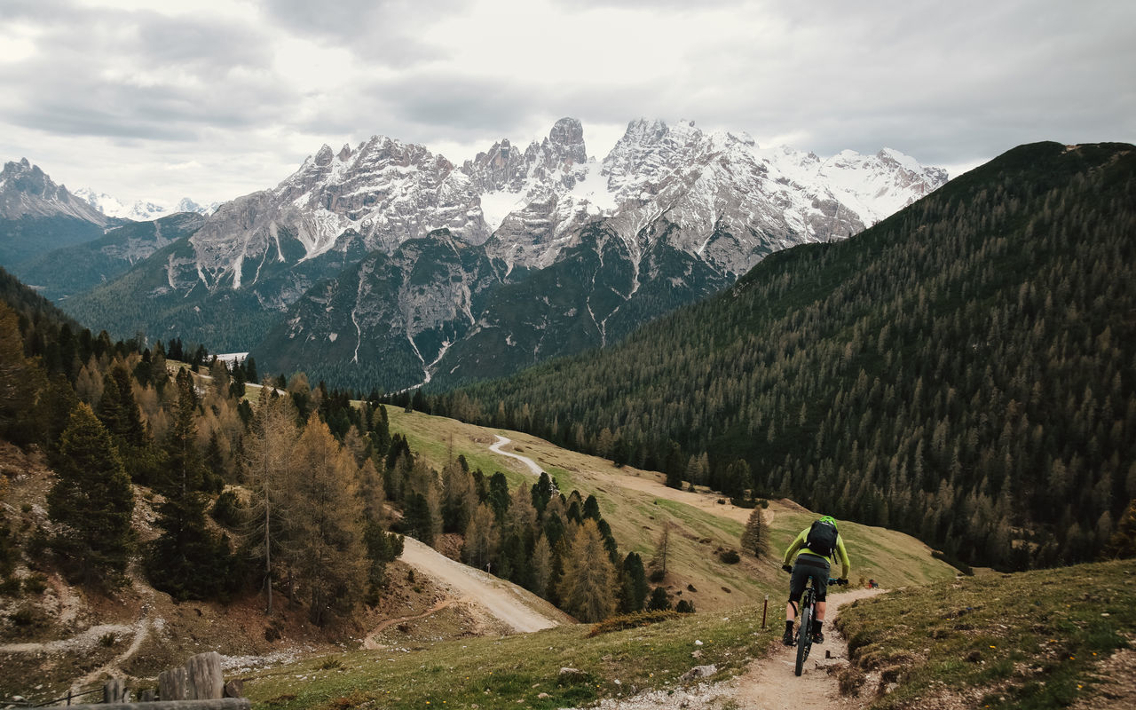 mountain, nature, mountain range, scenics, beauty in nature, real people, sky, adventure, tranquility, tranquil scene, lifestyles, landscape, snow, cloud - sky, leisure activity, backpack, rear view, cycling, day, outdoors, one person, winter, snowcapped mountain, men, cold temperature, tree, full length, slope, people