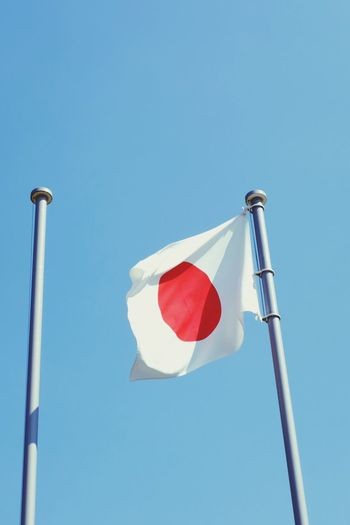 Low angle view of japanese flag against clear blue sky