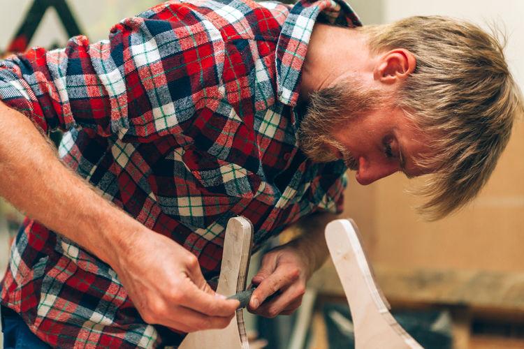 Craftsman working inside carpentry workshop studio using manual lime