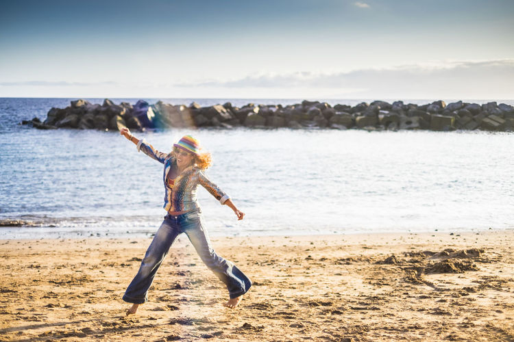 Full length of excited woman jumping at beach against sky