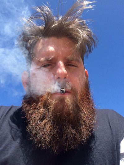 Portrait Of Man Smoking Against Sky