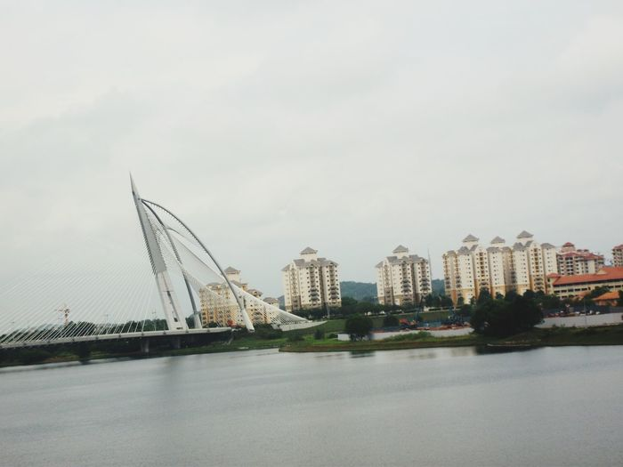Bridge over river by buildings against sky in city
