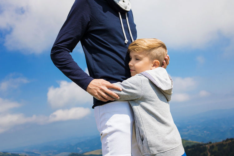Son Embracing Father Against Sky