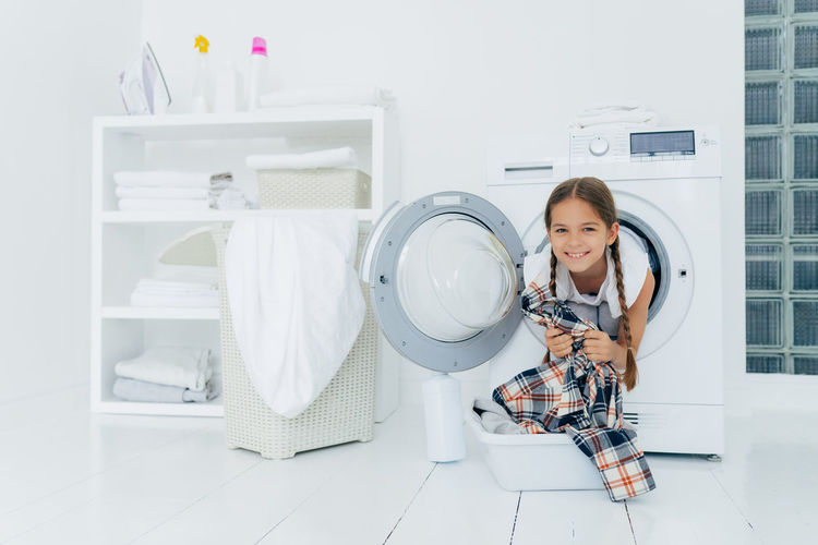 Portrait of smiling girl in washing machine at home