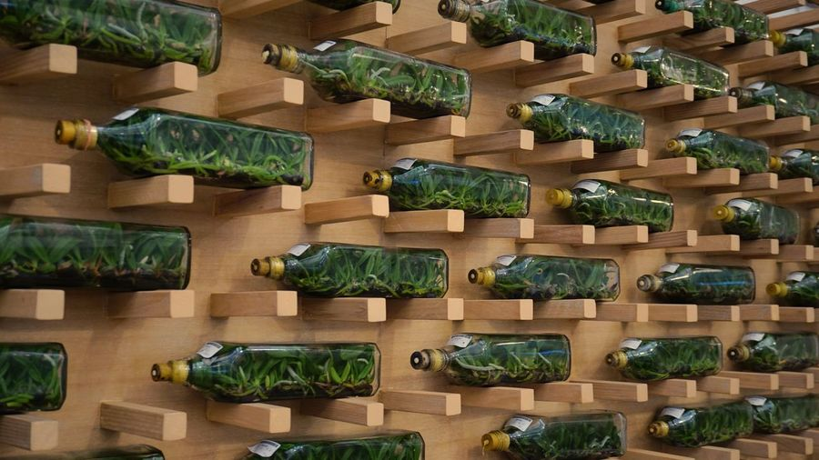 Orchid in glass bottles on wooden wall.