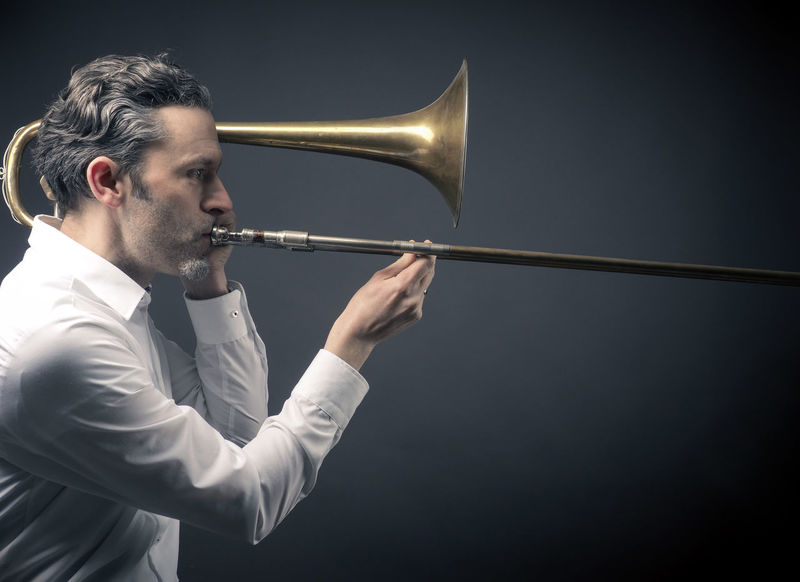 Musician with an old trombone on a dark studio background Excercising Sound Adult Adults Only Black Background Brass Classical Music Concentration Expertise Indoors  Instrument Men Music Musician Occupation One Man Only One Person Only Men People Playing Skill  Studio Shot Trombone Wind Instrument Young Adult
