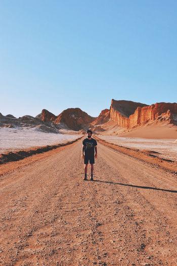 Full Length Of Man Standing On Dirt Road Against Clear Blue Sky At Atacama Desert