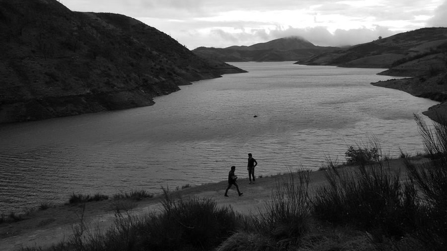 High angle view of silhouette male friends standing at lakeshore against mountains