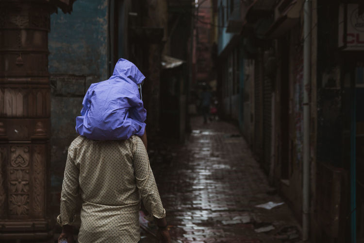 Rear view of man carrying baby on shoulder in alley