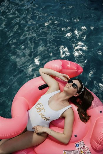 High angle view of woman floating in swimming pool
