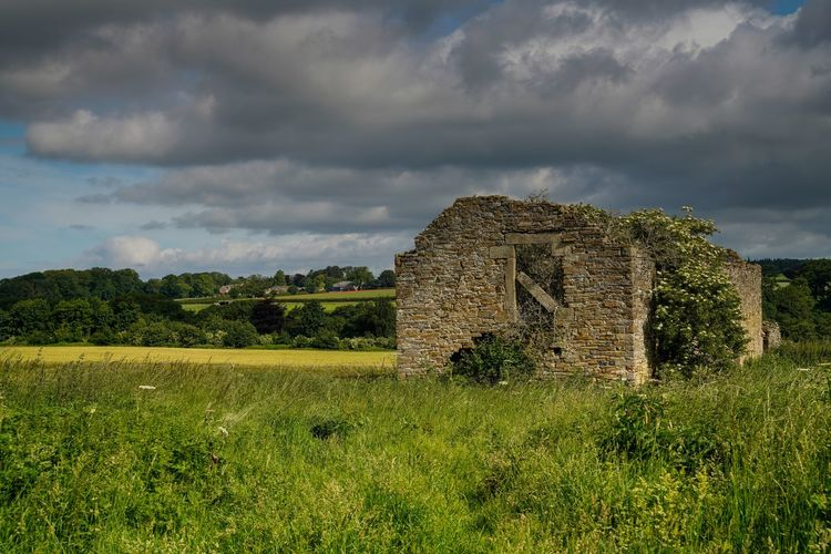 Old ruin on field against sky
