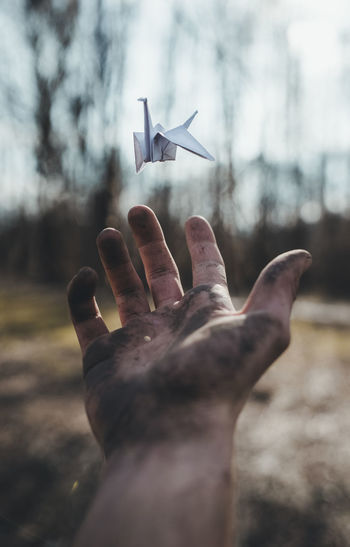 Cropped image of messy hand with origami