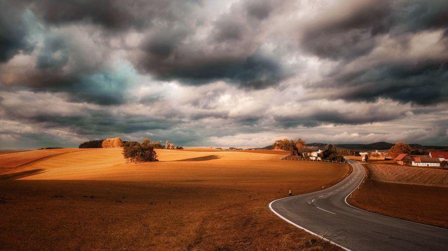 Road In Desert Against Cloudy Sky