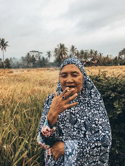 Portrait of senior woman smoking cigarette while standing at farm against sky
