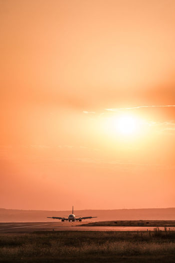 Air Vehicle Airplane Airport Beauty In Nature Cloud - Sky Dramatic Sky Environment Idyllic Landscape Mode Of Transportation Nature No People Orange Color Outdoors Scenics - Nature Silhouette Sky Sun Sunset Tranquil Scene Tranquility Transportation