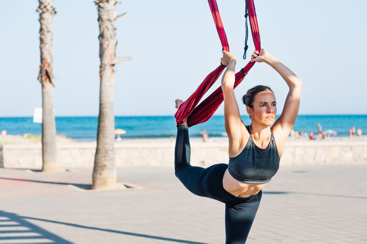 Mid adult woman exercising with textile at beach against clear sky