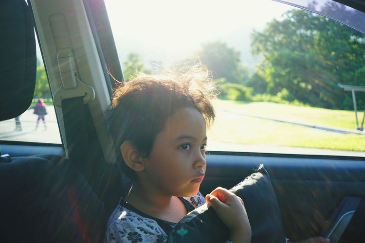 Close-up of young woman sitting in car