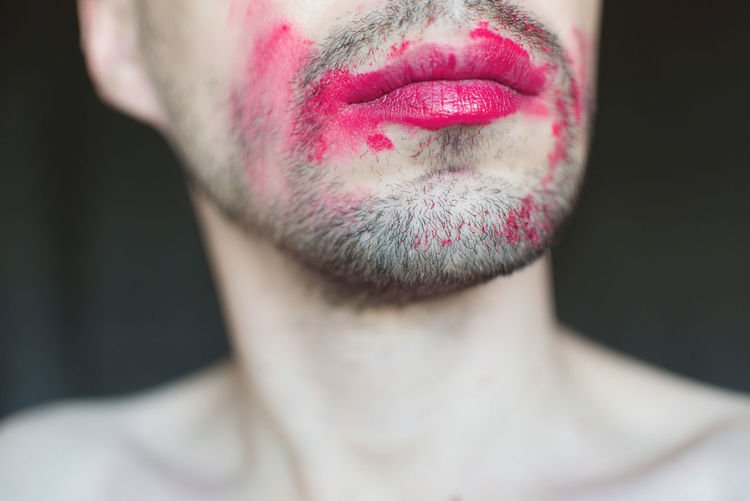 Midsection of transgender man with red lipstick