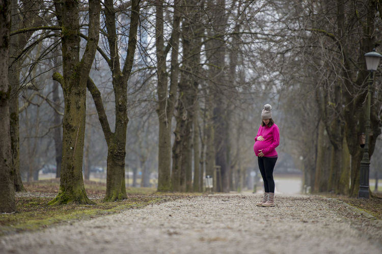 Woman running on footpath amidst trees in forest
