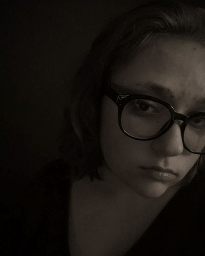 Looking At Camera Young Adult Portrait Black Background Front View Glasses ANGST Young Women Human Body Part Dark People One Person Close-up One Young Woman Only Adult Human Eye Eyesight Day