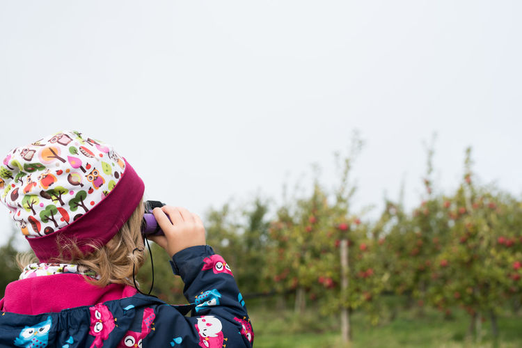 little girl observing the sky with a binocular Binoculars Child Childhood Copy Space Daylight Females Focus On Foreground Girls Green Trees Grey Sky Leisure Activity Nature Observing One Person Outdoors Real People Standing Warm Clothing Women